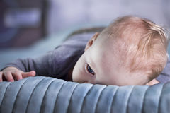 Пробуренный ребёнок лежа на кровати Спокойный младенческий ребенк на кровати Утомленный малыш Стоковые Изображения RF