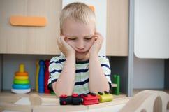 Пробуренный унылый мальчик сидя на таблице Стоковая Фотография RF