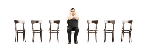 Пробуренный человек при чемодан сидя на работе стула ждать взаимо- Стоковые Изображения