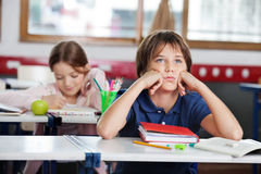 Пробуренный школьник смотря отсутствующее усаживание на столе внутри Стоковое Изображение RF