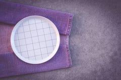 Проверенная белая плита и пурпурная скатерть стоковая фотография