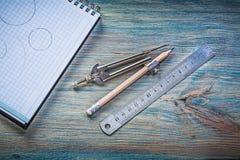 Проверенный карандаш рассекателя правителя тетради с прописями на винтажной деревянной доске Стоковые Фото