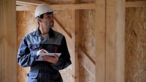 Проверка архитектора или построителя планирует в половинном построенном доме рамки тимберса Усмехаясь построитель на строительной акции видеоматериалы