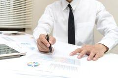 Проверка бизнесмена о цене и делать отчет о диаграммы финансов на офисе Стоковое фото RF