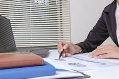Проверка бизнесмена серьезно анализирует коллег инвестора отчете о финансов обсуждая данные по диаграммы нового плана финансовые  Стоковая Фотография RF