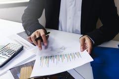 Проверка бизнесмена серьезно анализирует коллег инвестора отчете о финансов обсуждая данные по диаграммы нового плана финансовые  Стоковые Изображения RF