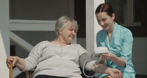 Проверка кровяного давления к пожилой медсестре женщины усмехающся и заботящ для старых людей Outdoors на солнечный день на съемк сток-видео