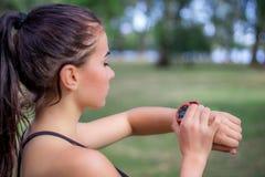 Проверки девушки Ftitness наблюдают отслежыватель на ее запястье руки во время бега Стоковое Изображение