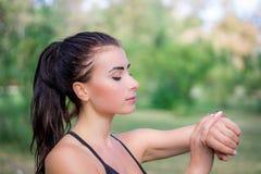 Проверки девушки Ftitness наблюдают отслежыватель на ее запястье руки во время бежать Стоковая Фотография RF