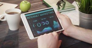 Проверять информацию о состоянии рынка интернета используя цифровую таблетку на столе сток-видео
