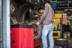 Проверять колесо автомобиля для ремонта на гараже автомобиля Стоковые Фото