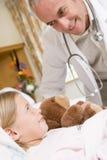 проверяющ доктора его пациент вверх по детенышам Стоковое фото RF