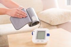 Проверяющ кровяное давление дома стоковая фотография