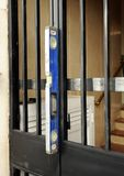 Проверяющ с уровнем правильное размещение входной двери металла стоковые изображения
