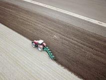 Проветрите взгляд вспахивать красный трактор на поле стоковое фото rf