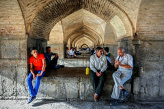 Провинция Ирана, Isfahan, Esfahan, мост Khajoo, Khaju - сентябрь 2016: Группа в составе местные люди отдыхая около моста свода стоковая фотография