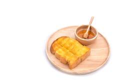 Провозглашанный тост хлеб с медом и ковшом меда на белой предпосылке Стоковые Фото