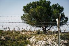 Проволочная изгородь бритвы в взгляде дневного света Международный пансионер между 2 странами стоковые изображения rf