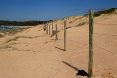 Проволочная изгородь на похожем на раковину пляже, центральном побережье NSW стоковое фото rf