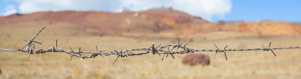 Провод колючки на ландшафте пустыни Стоковая Фотография RF