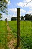 Проволочная изгородь бежать вдоль поля выгона Стоковое Фото