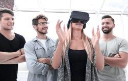 Прогрессивная девушка усмехаясь пока носящ стекла виртуальной реальности стоковая фотография