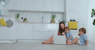 Прогрессивная молодая мать с 2 маленькими ребятами говорит с ее отцом через видеосвязь самомоднейшая технология видеоматериал
