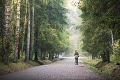 Прогулка девушки в лесе осени среди высоких деревьев с желтыми листьями Стоковые Фотографии RF
