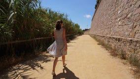 Прогулка женщины вдоль высокой каменной стены Monj акции видеоматериалы