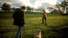 Прогулка женщины молодого человека после этого бежит с собакой на заходе солнца сток-видео