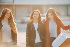 Прогулка 3 женщин вместе с бумажными хозяйственными сумками Стоковое Изображение