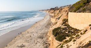 Прогулка людей вдоль широкого пляжа около towering скал в пляже Solana Стоковое Изображение RF