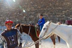 Прогулка людей на лошадях на пирамидах Египте Стоковое Изображение