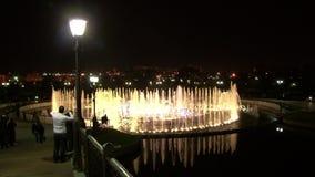 Прогулка людей на ноче около фонтанов танцев сток-видео