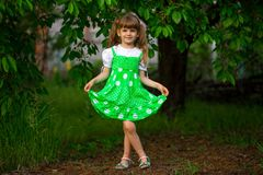 Прогулка маленькой девочки в зеленом саде в солнечном дне стоковое фото rf