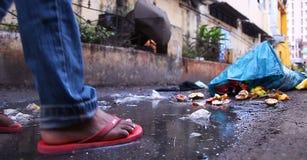 Прогулка молодого человека в пакостной воде в сельской местности голубые сумки отброса на дороге встают на сторону на внешнем Стоковые Фотографии RF