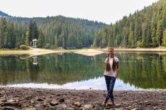 Прогулка молодой женщины около озера горы Стоковая Фотография