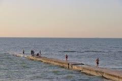 Прогулка некоторые людей и рыбы некоторые людей, на деревянной пристани, во время восхода солнца лета в Чёрном море стоковое фото