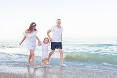 Прогулка родителей вдоль seashore с дочерью стоковое изображение