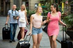 Прогулка девушек и волоча чемоданы Стоковые Фотографии RF