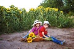 Прогулка детей около поля солнцецветов Концепция children& x27; приятельство s Стоковые Фотографии RF
