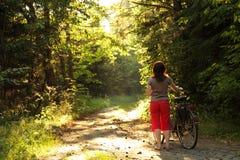Прогулка женщины велосипедиста в парке с велосипедами Стоковые Фотографии RF