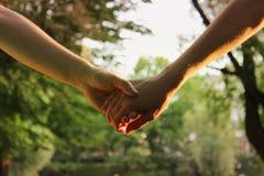 Прогулка 2 маленьких девочек держа руки в парке в вечере Стоковые Изображения