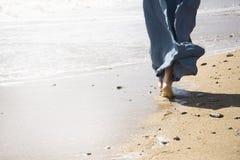 Прогулка молодой женщины на пляже Стоковое фото RF