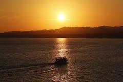 Прогулка на яхте во время захода солнца над морем и Mounties Стоковое Изображение