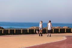 Прогулка океана девушек катаясь на коньках пляжная Стоковые Фото