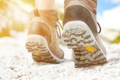 Прогулка hiker женщины на скалистой земле день солнечный Trekking ботинки Пирофакел объектива Успешный backpacker камень шаг Стоковое Фото