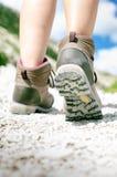 Прогулка hiker женщины на скалистой земле день солнечный Trekking ботинки Пирофакел объектива Успешный backpacker камень шаг Стоковые Фото