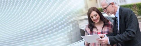 Продавец автомобилей давая объяснения на таблетке к молодой женщине, световой эффект знамя панорамное стоковое фото rf
