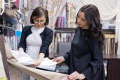 Продавец - дизайнер ткани советует покупателю женщины Стоковые Изображения